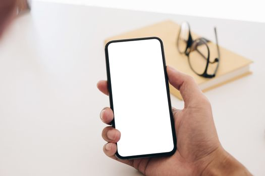 Top view man sitting and holding blank screen mock up mobile pho