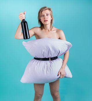 Coronavirus quarantine. Crazy quarantine. Desperate woman in pillowdress holding a wine bottle isolated on blue background. Pillow challenge