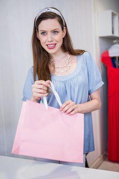 Brunette at till with shopping bag