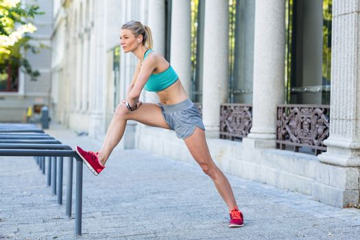 A beautiful woman stretching her leg against pipes