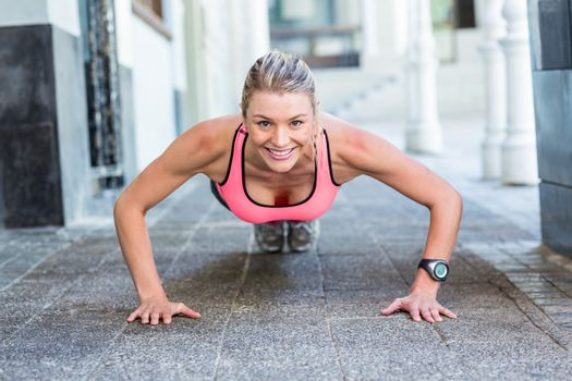 A pretty woman doing push-ups on the floor