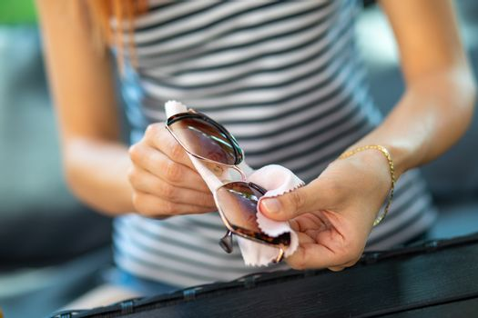 Wiping sunglasses - Woman cleaning sun glasses with micro fiber