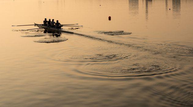 Team of four rowers practice in racing canoe