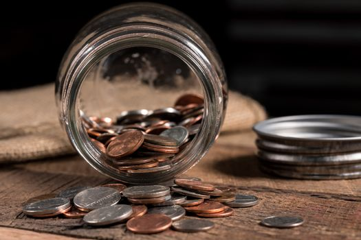 Glass mason jar with a few coins inside to illustrate poverty