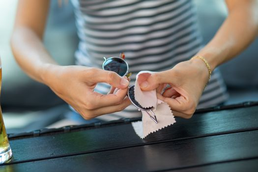 Wiping sunglasses - women cleaning sun glasses with micro fiber