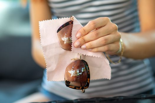 Woman hands cleaning sun glasses with micro fiber wipe