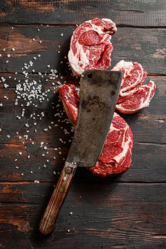 raw cowboy steak and Chuck eye roll with seasonings on old butchery wood background, prime rib