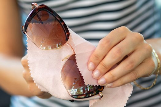 Women hands cleaning protective sunglasses with micro fiber wipe