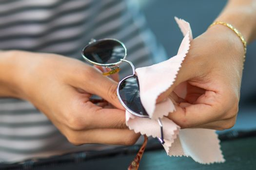 Woman with hands cleaning sun glasses with micro fiber wipe