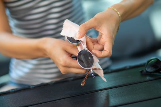 Woman hands wiping sun glasses with micro fiber wipe