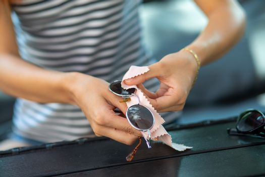 Hands cleaning sun glasses with micro fiber wipe