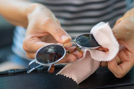 Woman hands cleaning and wiping sun glasses with micro fiber wip