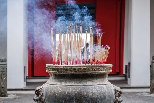 Incense sticks in ashes bucket in Temple Thialand