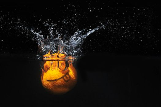 Smile orange with splashes of water on a black background