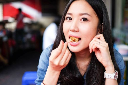 Woman eating Chinese Shanghainese steamed dumpling buns