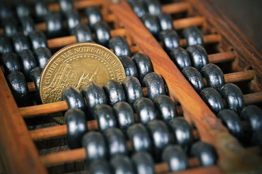 vintage wooden abacus with coin on wood background