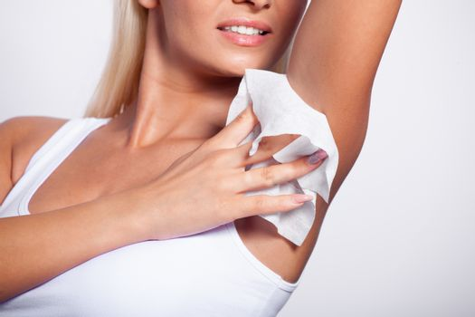 Young woman wipes the armpit with wet wipes