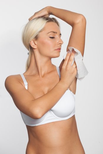 Young woman celaning armpit with wet wipes
