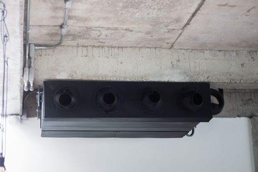 Black air conditioner on ceiling concrete, stock photo