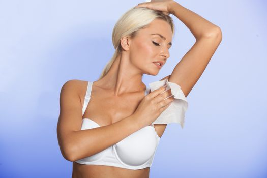 Woman celaning armpit with wet wipes