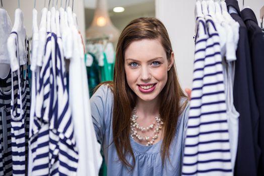 Brunette smiling through clothes rail