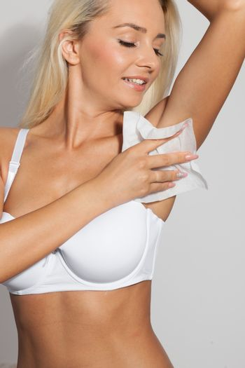 Young woman wipes the armpit
