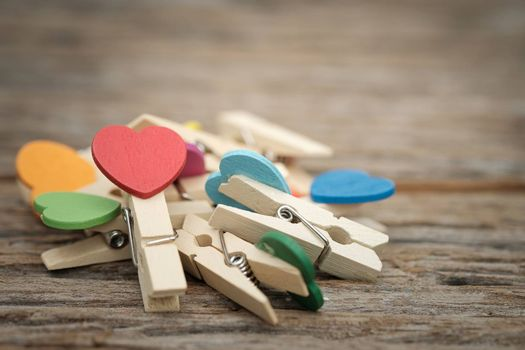 Heart clothespin pile on wooden background with space to write. Valentine concept, Vintage tone, AF point selection.