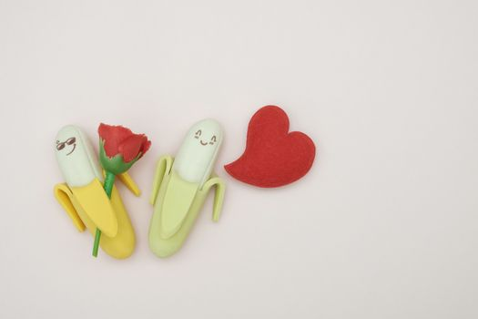 Two rubber banana and heart-shape pillow on pink background, valentine concept.