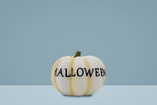 Halloween pumpkin on blue background. Halloween idea concept.