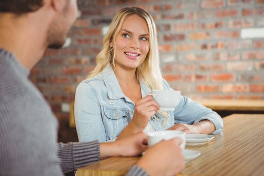 Smiling blonde having coffee with friend at coffee shop