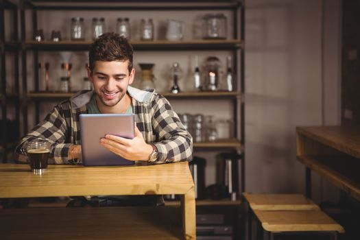 Smiling hipster having coffee and using tablet computer at coffee shop