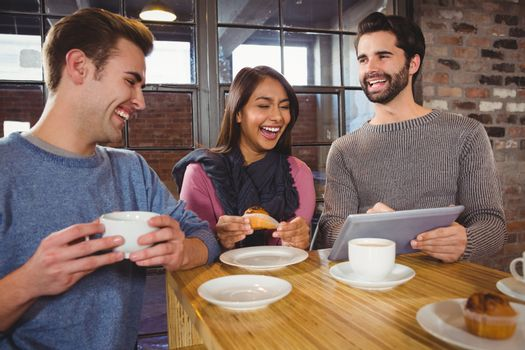 Group of friends enjoying a dessert with tablet in a cafe