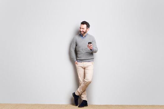 Full body cool businessman holding cellphone against gray wall