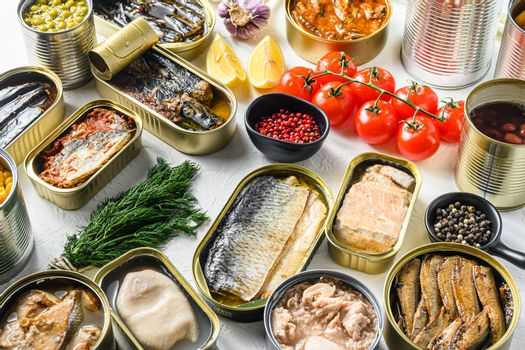 Different canned conserve products in tin cans. with fresh organic ingridients Saury, mackerel, sprats, sardines, pilchard, squid, tuna pinapple, corn, peas, mango , beans, over white textured background side view