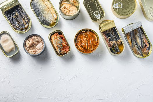 Cans with different preserve of fish and conserve seafood, opened and closed cans with Saury, mackerel, sprats, sardines, pilchard, squid, tuna, over white stone surface top view space for text