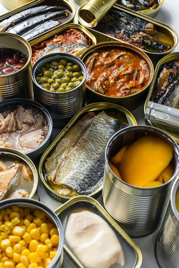 Tin cans for processed food cans conserve Saury, mackerel, sprats, sardines, pilchard, squid, tuna pinapple, corn, peas, mango , beans, over white textured background close up side view