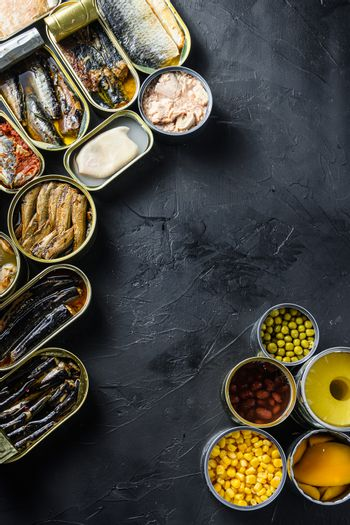 Canned conserve products in tin cans. with fresh organic ingridients Saury, mackerel, sprats, sardines, pilchard, squid, tuna pinapple, corn, peas, mango , beans, over black stone textured background top view space for text vertical corner concept