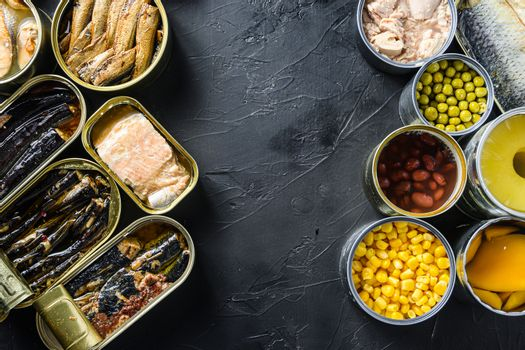 Canned conserve products in tin cans. with fresh organic ingridients Saury, mackerel, sprats, sardines, pilchard, squid, tuna pinapple, corn, peas, mango , beans, over black stone textured background top view space for text side by side concept