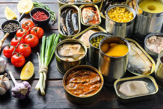 Different canned conserve products in tin cans. with fresh organic ingridients Saury, mackerel, sprats, sardines, pilchard, squid, tuna pinapple, corn, peas, mango , beans, over old wood dark textured background side view