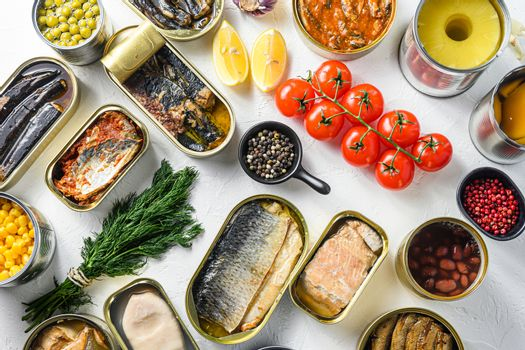 Different canned conserve products in tin cans. with fresh organic ingridients Saury, mackerel, sprats, sardines, pilchard, squid, tuna pinapple, corn, peas, mango , beans, over white textured background top view.