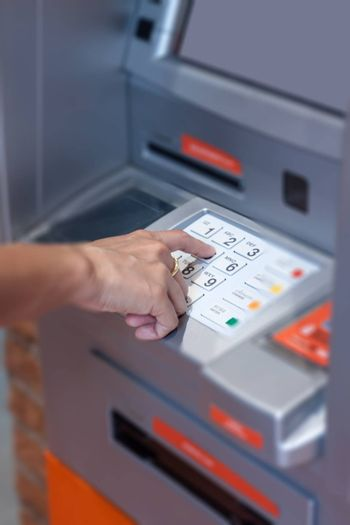 Close up of hand entering pin code at Automated Teller Machine, stock photo
