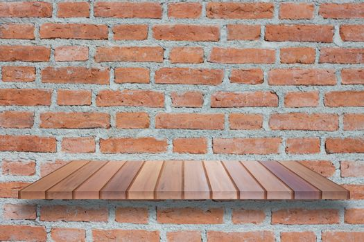 Brown wooden shelf on brick wall. For product display