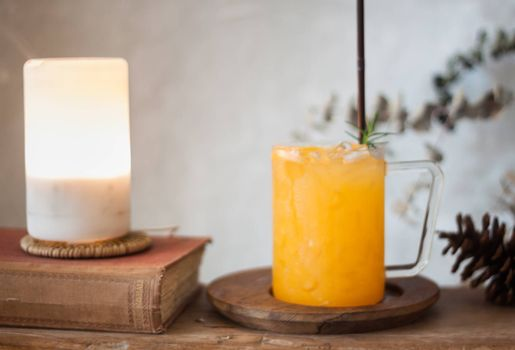 Glass of fresh orange juice with slice on wooden table