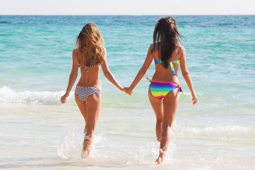Happy girls running through the water at the beach, female friends, vacation fun