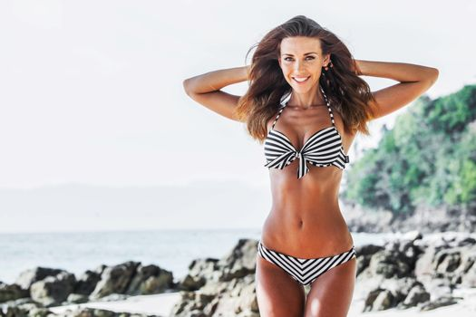 Happy tanned girl in bikini at seaside, blue sea and stony beach on background