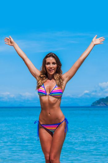 Beach summer holidays woman in happy freedom concept with arms raised. Woman wearing bikini enjoy vacation at seaside