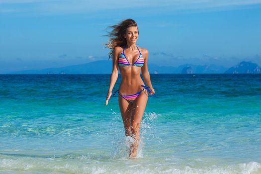 Beautiful happy girl in bikini running in tropical sea waves