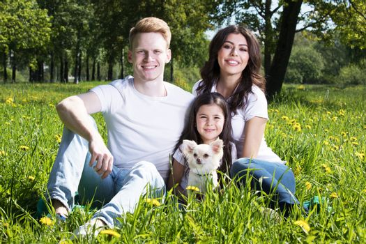 Happy smiling family of parents and daughter with pet dog in summer park