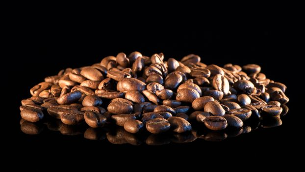 Coffee beans on a black mirror background close-up.