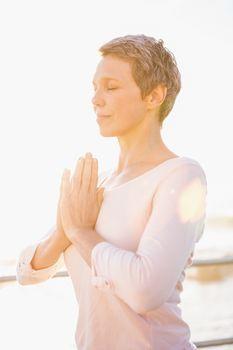 Peaceful sporty woman meditating at promenade